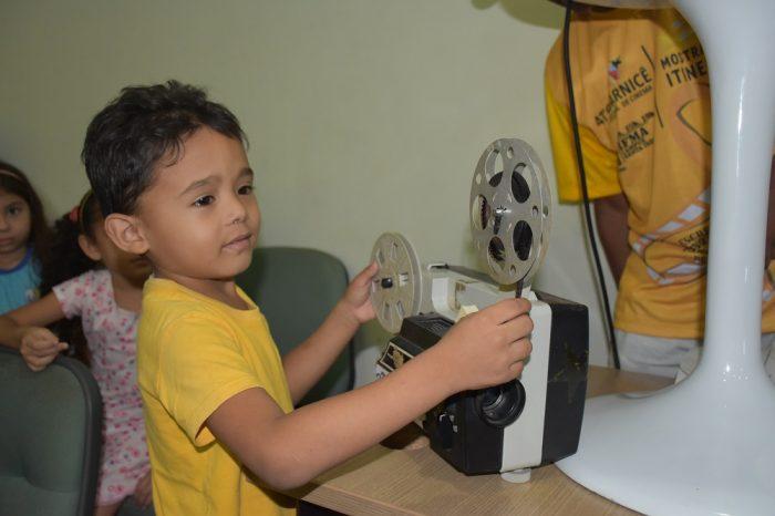 Criança observa e toca projetor de cinema antigo em exposição no auditório.