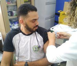 Mulher com jaleco branco aplica vacina no braço de um homem sentado em uma cadeira.